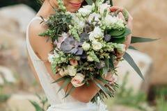 Ramalhete do casamento nas mãos do ` s da noiva foto de stock royalty free