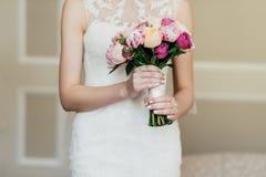 Ramalhete do casamento nas mãos do ` s da noiva Noiva magro no vestido branco que guarda flores bonitas nas mãos, indo casar-se,  fotografia de stock royalty free