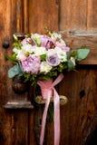 Ramalhete do casamento que pendura em um puxador da porta velho no fundo de portas de madeira antigas foto de stock royalty free