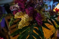 Ramalhete do lilás branco e roxo em uma tabela de madeira no café imagens de stock