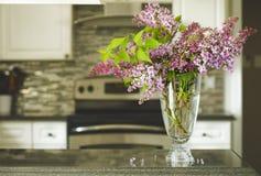 Ramalhete do lilás na mesa de cozinha, interior da cozinha borrado para trás Fotografia de Stock