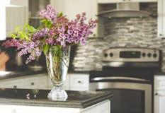 Ramalhete do lilás na mesa de cozinha, interior da cozinha borrado para trás Foto de Stock Royalty Free