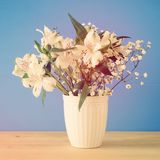 ramalhete do verão das flores brancas no vaso sobre a tabela de madeira e o fundo azul Fotografia de Stock Royalty Free