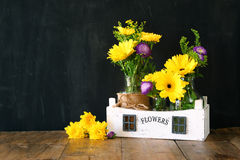 Ramalhete do verão das flores na tabela de madeira e no fundo de madeira do quadro-negro Copie o espaço Fotos de Stock