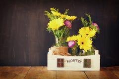 Ramalhete do verão das flores na tabela de madeira e no fundo de madeira do quadro-negro Copie o espaço Imagens de Stock Royalty Free