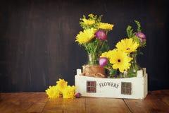 Ramalhete do verão das flores na tabela de madeira e no fundo de madeira do quadro-negro Copie o espaço Imagem de Stock Royalty Free