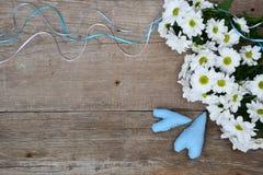 Ramalhete dos crisântemos brancos com dois corações azuis na madeira Foto de Stock Royalty Free