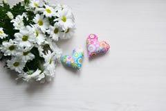 Ramalhete dos crisântemos brancos com dois corações pequenos no fundo de madeira branco Fotos de Stock