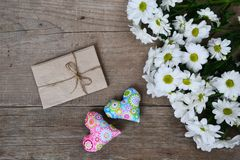 Ramalhete dos crisântemos brancos com envelope e dos dois corações na madeira Fotos de Stock Royalty Free