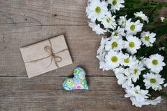 Ramalhete dos crisântemos brancos com envelope e um coração na madeira Imagem de Stock Royalty Free