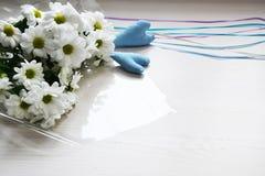 Ramalhete dos crisântemos brancos com fitas e de dois corações azuis no fundo branco Fotos de Stock