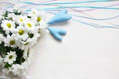 Ramalhete dos crisântemos brancos com fitas e de dois corações azuis no fundo branco Foto de Stock Royalty Free