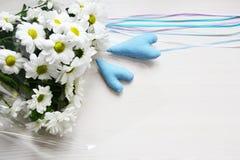 Ramalhete dos crisântemos brancos com fitas e de dois corações azuis no fundo branco Imagens de Stock Royalty Free