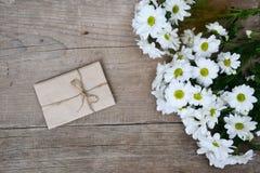 Ramalhete dos crisântemos brancos com o envelope na madeira Imagens de Stock Royalty Free