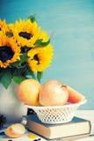 Ramalhete dos girassóis no vaso branco com maçãs Fotografia de Stock