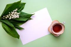 Ramalhete dos lírios do vale, de um copo do chá e de uma folha de papel fotografia de stock