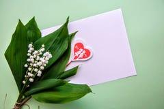 Ramalhete dos lírios do vale, de um coração e de uma folha de papel fotografia de stock