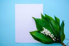 Ramalhete dos lírios do vale e de uma folha de papel em um fundo azul foto de stock royalty free