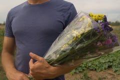 Ramalhete dos statis violetas, amarelos, cor-de-rosa e brancos nas mãos do ` s do homem Imagem de Stock Royalty Free