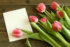 Ramalhete dos tulips com o cartão em branco em de madeira velho Fotografia de Stock