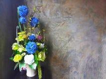 Ramalhete em um vaso branco com um estilo da parede do cimento imagens de stock