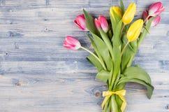 Ramalhete fresco de tulipas amarelas e vermelhas na placa de madeira chique gasto azul com espaço da cópia imagens de stock royalty free