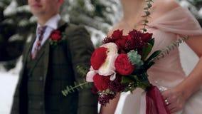Ramalhete levando da noiva das flores feitas das rosas brancas e vermelhas Pares do casamento que andam guardando as mãos na flor vídeos de arquivo
