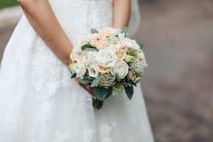 Ramalhete nas mãos do ` s da noiva, imagem horizontal do casamento da beleza, close-up imagens de stock royalty free
