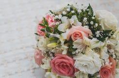 Ramalhete nupcial bonito, alianças de casamento do ouro branco em flores fotos de stock royalty free