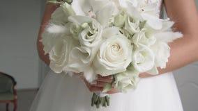 Ramalhete nupcial branco bonito das rosas em um interior brilhante filme
