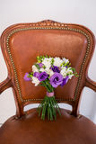Ramalhete nupcial branco e roxo em uma cadeira marrom fotografia de stock
