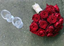 Ramalhete nupcial com as rosas vermelhas ao lado dos vidros de vinho Fotos de Stock