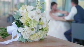 Ramalhete nupcial das flores na tabela com os recém-casados blured no fundo vídeos de arquivo
