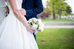 Ramalhete nupcial delicado bonito das rosas brancas e das flores nas mãos da noiva Imagens de Stock Royalty Free