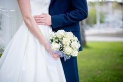 Ramalhete nupcial delicado bonito das rosas brancas e das flores nas mãos da noiva Imagem de Stock Royalty Free