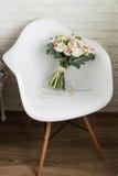 Ramalhete nupcial delicado em uma cadeira imagem de stock
