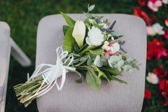 Ramalhete nupcial do casamento com as rosas na cadeira imagens de stock royalty free