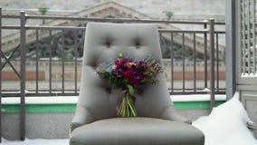 Ramalhete nupcial do casamento das flores na cadeira no terra?o do inverno no dia snowly filme