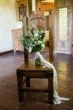 Ramalhete nupcial rústico em uma cadeira de madeira dentro foto de stock
