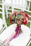Ramalhete nupcial vermelho impressionante na cadeira branca Cerimónia de casamento Mistura de plantas carnudas, de orquídeas e de Fotografia de Stock Royalty Free