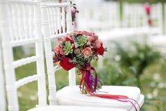 Ramalhete nupcial vermelho impressionante na cadeira branca Cerimónia de casamento Mistura de plantas carnudas, de orquídeas e de Foto de Stock