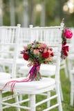 Ramalhete nupcial vermelho impressionante na cadeira branca Cerimónia de casamento Mistura de plantas carnudas, de orquídeas e de Imagens de Stock Royalty Free