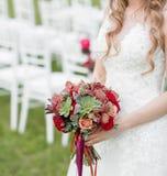 Ramalhete nupcial vermelho impressionante na cadeira branca Cerimónia de casamento Mistura de plantas carnudas, de orquídeas e de Fotos de Stock Royalty Free