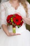 Ramalhete nupcial vermelho nas mãos de Fotografia de Stock