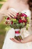 Ramalhete nupcial vermelho nas mãos de Fotografia de Stock Royalty Free