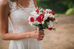 Ramalhete pequeno do casamento nas mãos do ` s da noiva Fotos de Stock Royalty Free