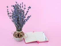 Ramalhete perfumado da alfazema seca com as flores roxas pequenas em uma pena cerâmica bonita do vaso e de esferográfica perto do foto de stock