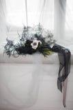 Ramalhete preto à moda amarrado com uma fita preta em um pano branco imagens de stock