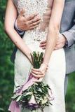 Ramalhete roxo do casamento nas mãos da noiva O indivíduo está abraçando a menina Vista traseira Imagens de Stock