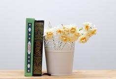 Ramalhete santamente dos livros e dos narcisos amarelos do Corão no vaso na aba de madeira Fotografia de Stock Royalty Free